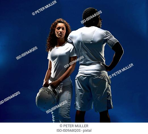 Studio portrait of male and female with football helmet