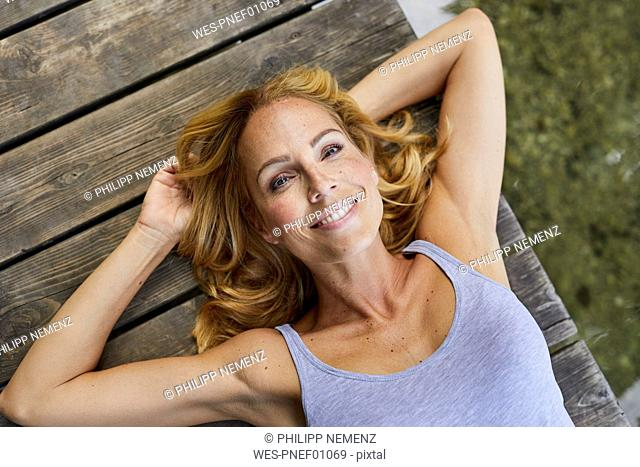 Portrait of smiling blond woman lying on wooden jetty at a lake