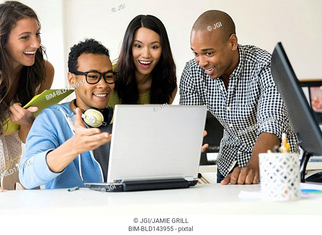 Business people working together on laptop in office