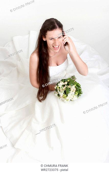 adult, angry, beautiful, bouquet, bride, brunette, call, Caucasian, cell, dress, expression, face, female, girl, gown, hair, mobile, one, person, phone, studio