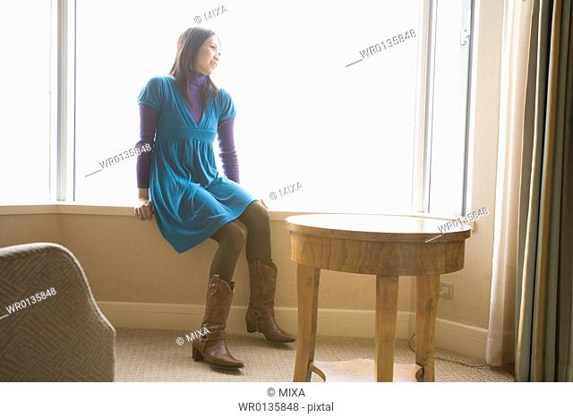 Young woman sitting in hotel room
