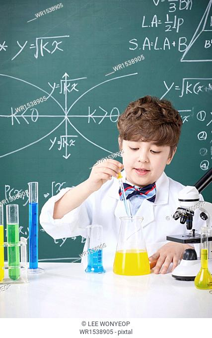 a young boy doing chemistry in front of a chalk board