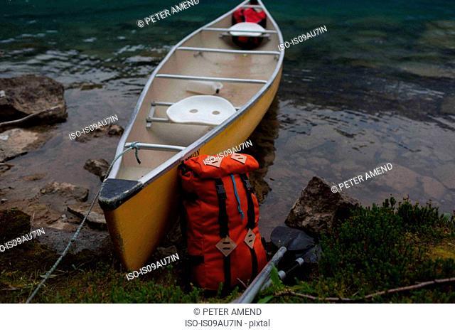 Orange colour backpack leaning against yellow canoe, Moraine lake, Banff National Park, Alberta Canada