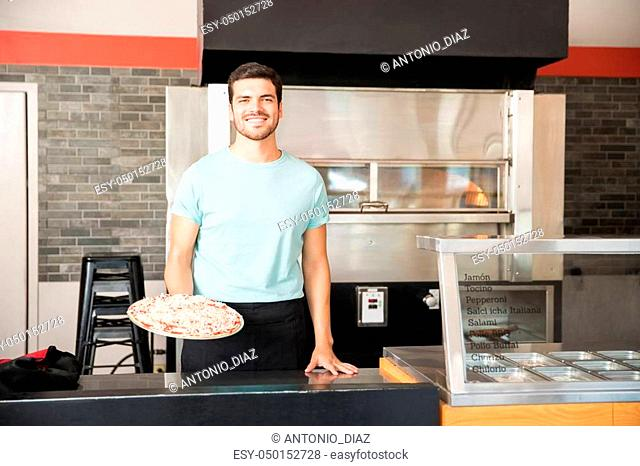 Confident chef waiter holding cooked cheese pizza standing at pizza shop counter smiling looking at camera