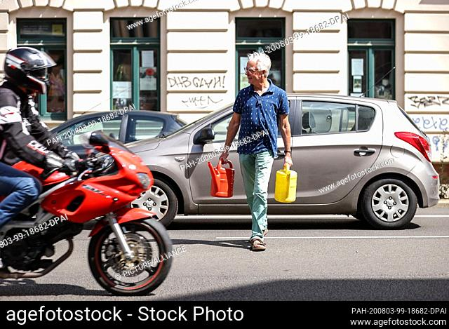 21 July 2020, Saxony, Leipzig: Uwe Buckendahl walks with two watering cans over the busy Lützner Straße to water a street tree