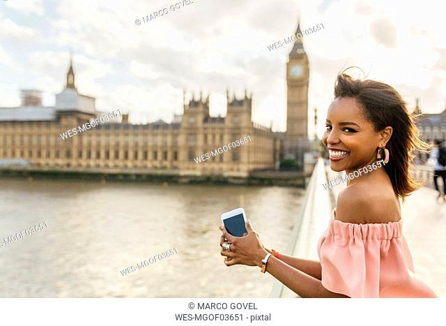 UK, London, portrait of smiling woman on Westminster Bridge