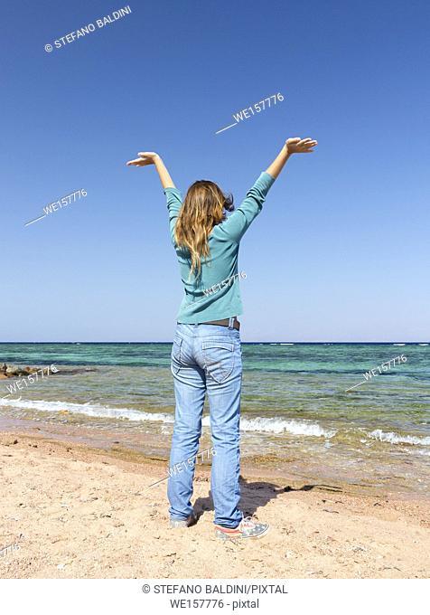 Teenage girl on the beach with arms raised, Dahab, Egypt