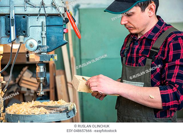 Carpenters with electric drill machine drilling wooden board at workshop. Profession, carpentry and woodwork concept