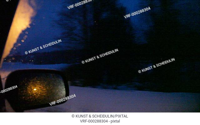 POV shot of a car driving on a country lane through a village in northern Sweden at dusk: looking through the side window we see houses decorated with fairy...