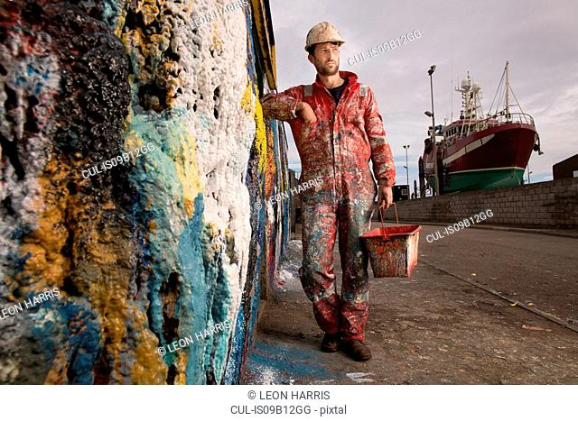 Male ship painter holding paint can leaning against paint splattered wall