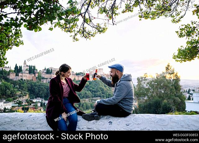 Coupleclinking drinks with Alhambra in background, Granada, Spain