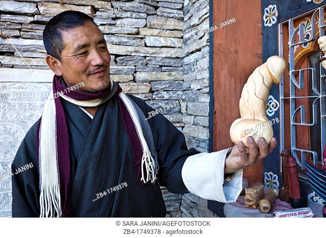 Local craftsman with a phalluses made of wood that are meant in Bhutan fertility and protection to the family from evil, Thimphu, Bhutan, Asia