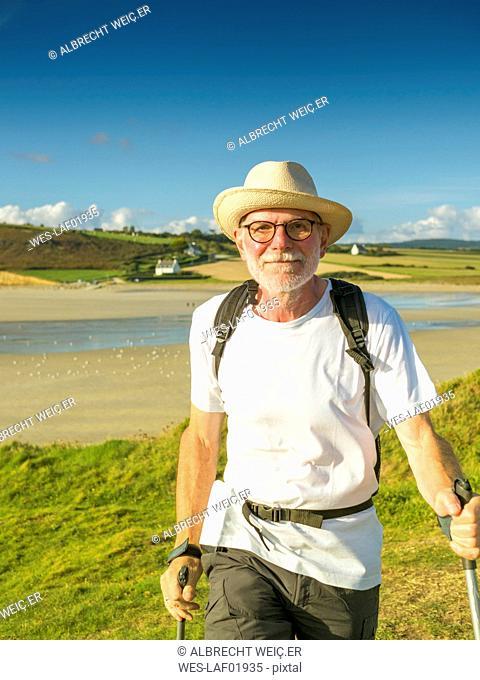 France, Bretagne, Active senior hiking on the beach of Treguer