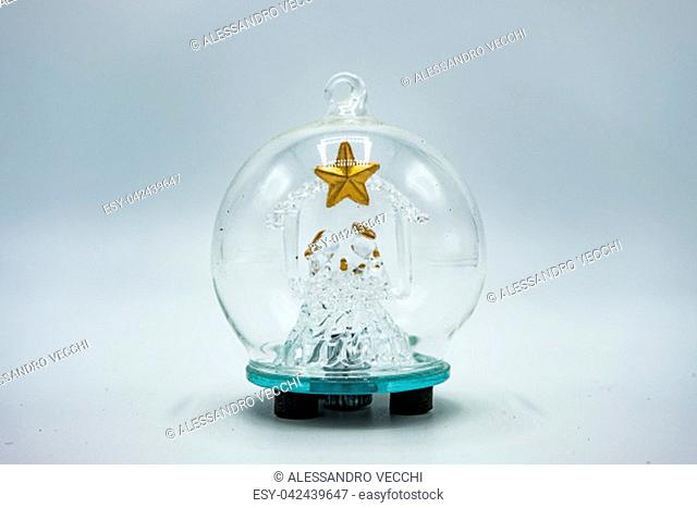 Crystal bauble with transparent Christmas tree inside with golden star isolated on white background