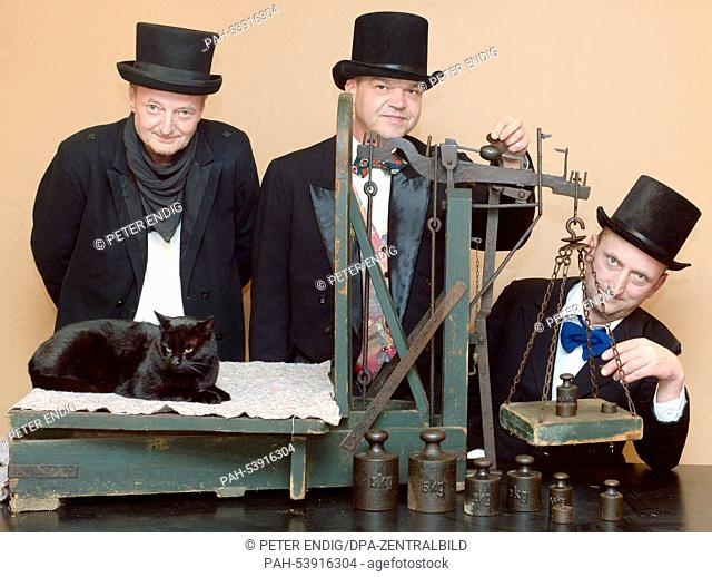 """The """"""""cat weigher"""""""" (L-R) Jens Lommatzsch, Jens Kopra and Jonny May way male cat Nero during the traditional """"""""cat weighing"""""""" at the Christmas Market in the..."""