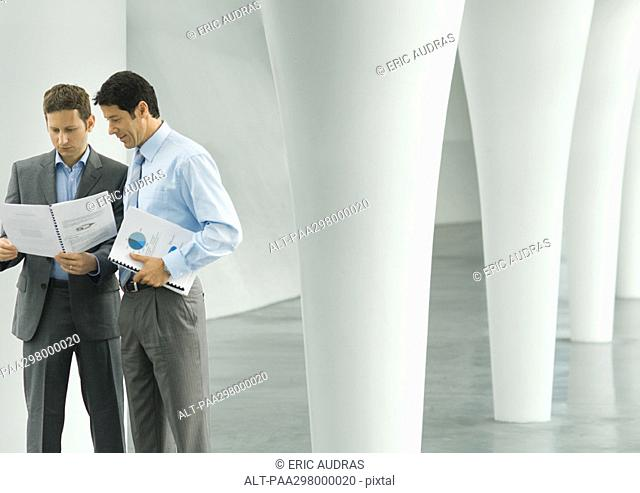 Two businessmen looking at documents in lobby