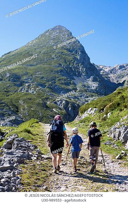 Family hiking in the Ándara massif, mountain of La Pica de Mancondiu in background. Picos de Europa National Park, Cantabria, Spain