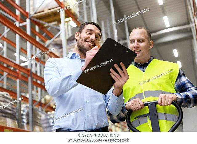 businessman with clipboard and loader at warehouse