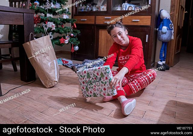 girl receiving Christmas gifts under the tree