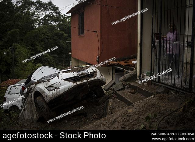 03 June 2020, El Salvador, Santo Tomás: A woman is standing in her house in the community of Panchimalco, in front of it are destroyed vehicles after heavy...