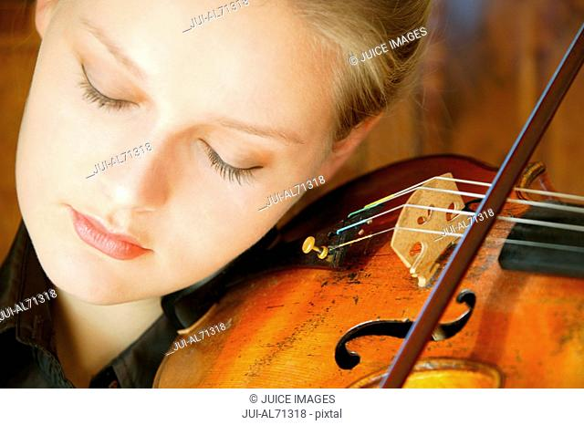 Portrait of a young woman playing a violin, (violin: built in 1770 by Paulus Castello, Genova)