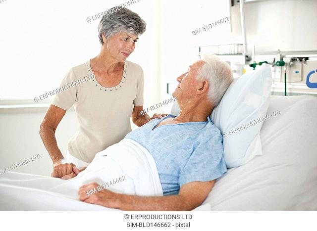 Wife comforting husband in hospital bed