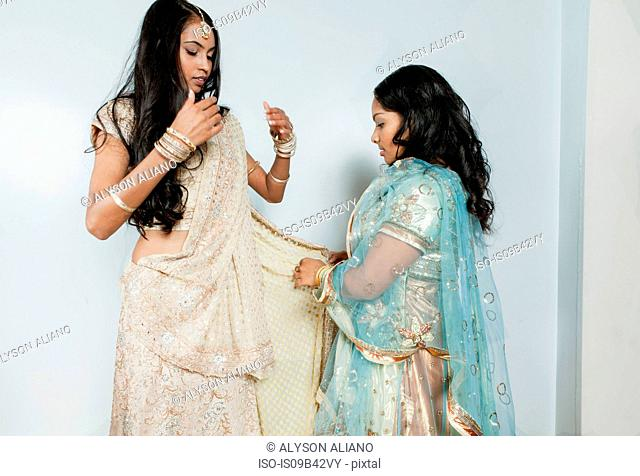 Young woman helping friend dress in traditional Indian costume