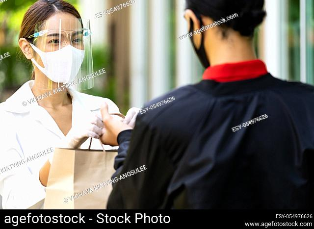 Portrait of atrractive asian woman give bakery grocery bag to delivery man to deliver it to customer make online order. Food delivery service concept in new...