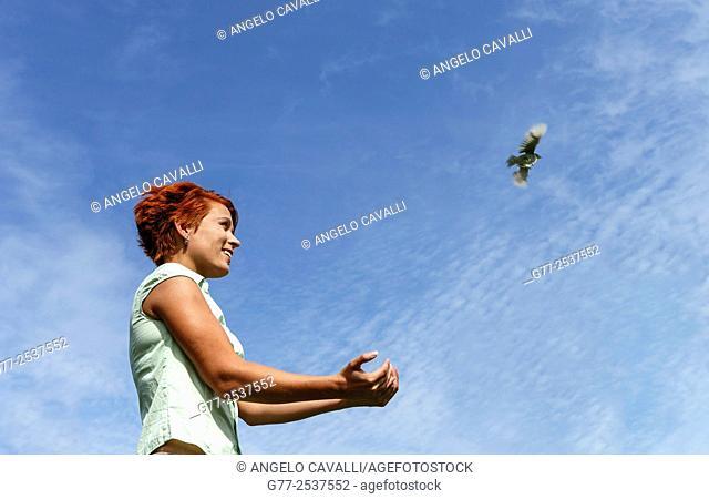 Woman releasing a bird. Budapest, Hungary
