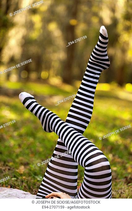 A partial view of a woman's legs, pointing up, wearing striped black & white stockings