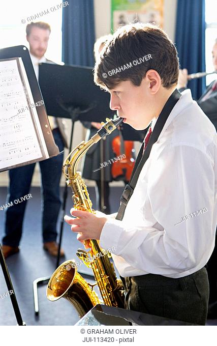 Middle school student playing saxophone at sheet music in music class