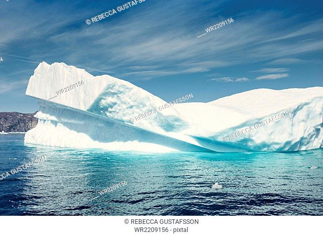 Scenic view of icebergs melting in sea against sky