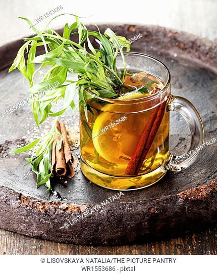 Tarragon hot drink tea with honey, lemon and cinnamon on dark background