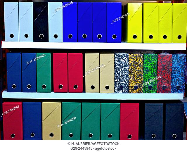 Carboards files of different colors lined on shelves in good order in an office