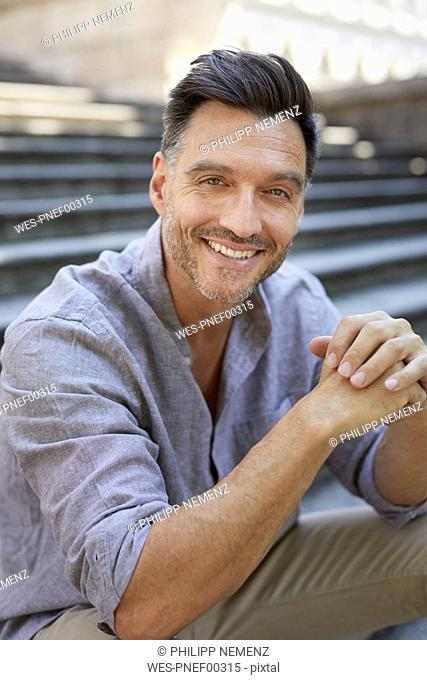 Portrait of laughing mature man  sitting on stairs