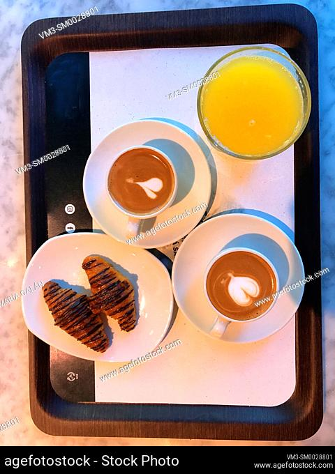 Two cups of coffee with croissants and orange juice. View from above