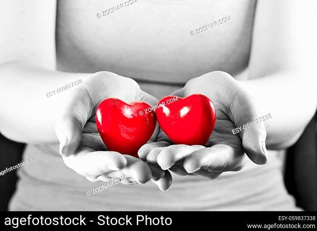 Two hearts in woman hands. Love giving, care, health, protection concept. Black and white