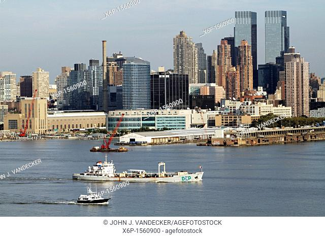 Boats on the Hudson River passing passing Manhattan skyline  The workboat in the foreground is a NYC Department of Environmental Protection sludge boat which...