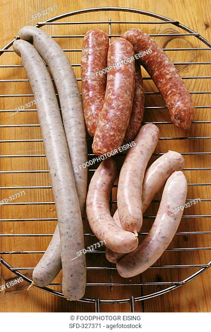 Various fresh sausages on a grill rack