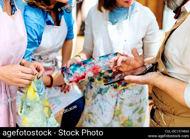 Four people in creative studio, holding painted fabric, looking at digital tablet, mid section