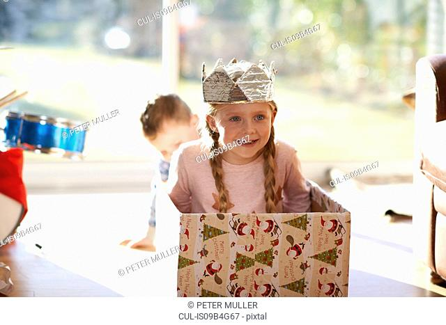 Girl sitting in cardboard box at christmas