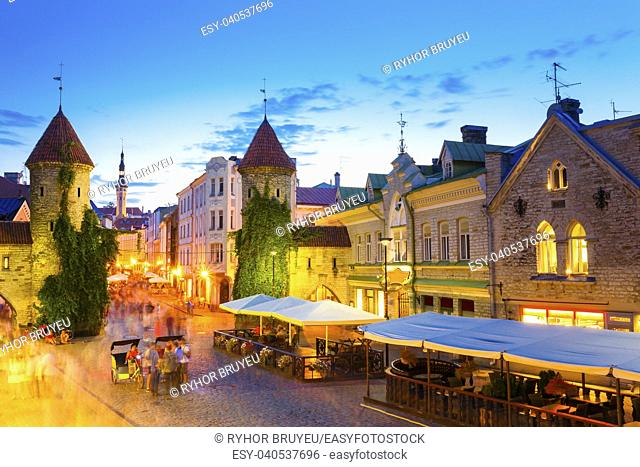 Tallinn, Estonia. People Walking Near Famous Landmark Viru Gate In Street Lighting At Evening Or Night Illumination. Popular Touristic Place In Sunny Summer...