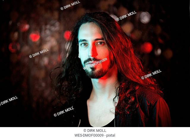 Portrait of bearded long-haired young man in red light