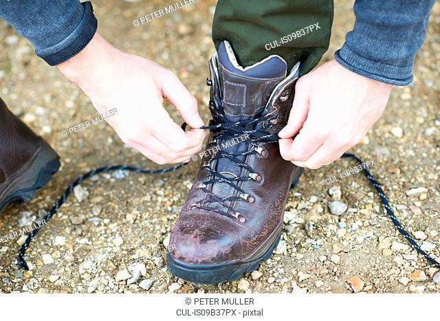 Cropped view of man tying shoe lace on hiking boot