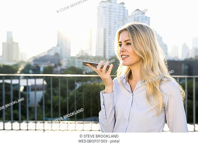 Blonde business woman speaking into smartphone on city rooftop