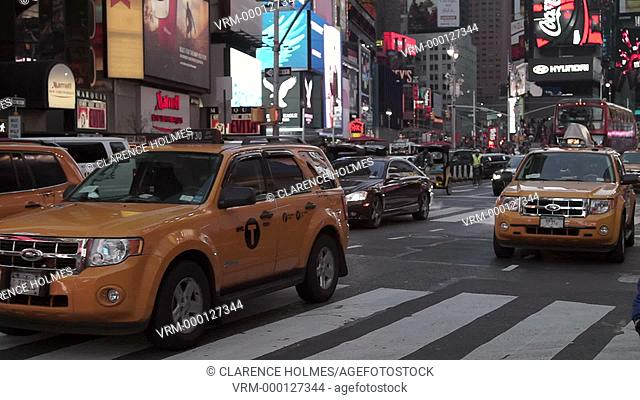 Traffic moving through Times Square on 7th Avenue at dusk in New York City