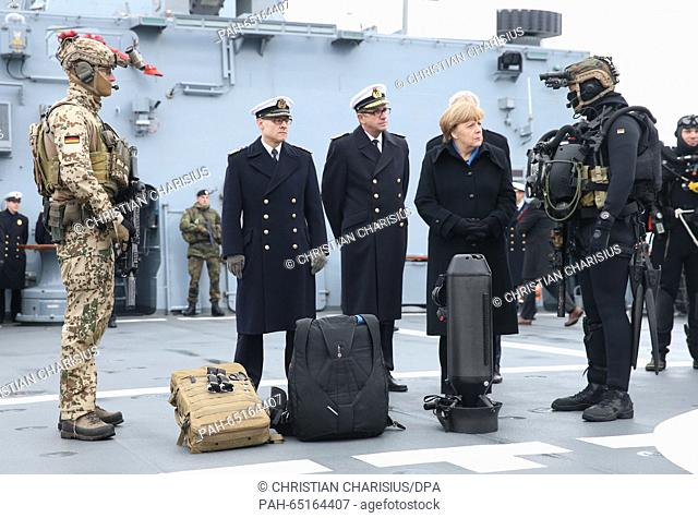 German Chancellor Angela Merkel speaking to a frogman on the deck of the corvette Braunschweig at the naval base in Kiel, Germany, 19 January 2016