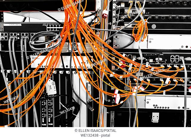 Fiber cables plugged into a high end router machine at a computer data center