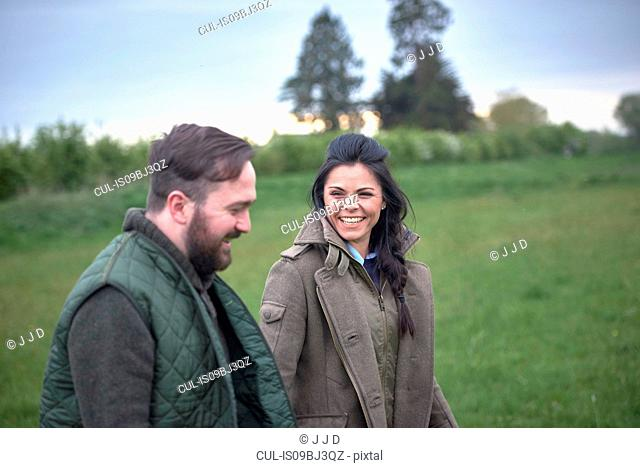 Woman and man walking and laughing in field