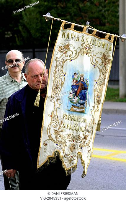 CANADA, TORONTO, 17.08.2008, A man holds a religious banner with an image of the Virgin Mary during a procession for the Feast of the Assumption
